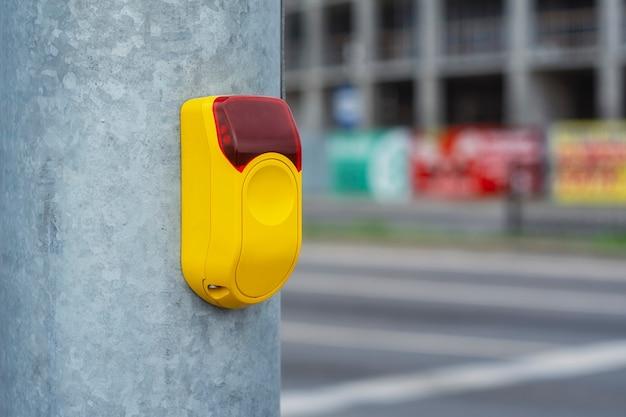 Желтая кнопка на светофоре для пешеходов на фоне дороги.