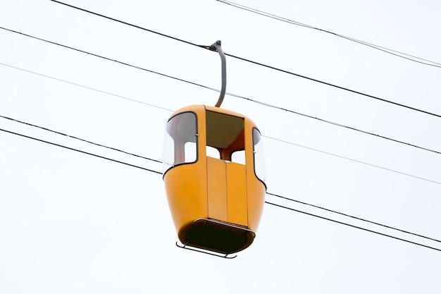 Желтая кабина канатной дороги на высоте. высотный транспорт для доставки людей в горы