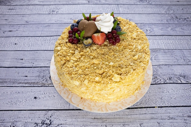 Yellow cake decorated with berries on a white wooden table