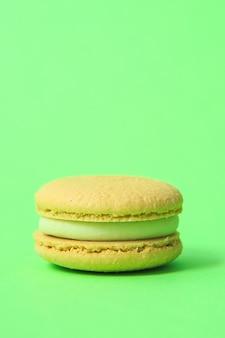 Желтый торт macaron или миндальное печенье на зеленой стене. разноцветное миндальное печенье. французский макарун