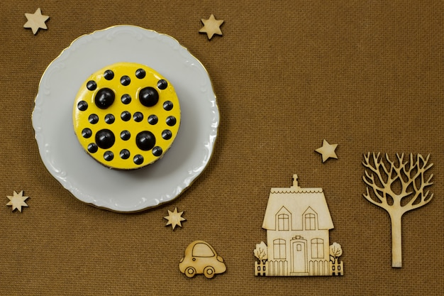 Yellow cake on a white platter. on a dark background icons: wood, house, car