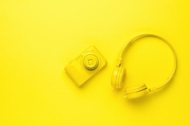 노란색 배경에 노란색 카메라와 노란색 헤드폰. 단색화. 창의적인 이미지. 플랫 레이.