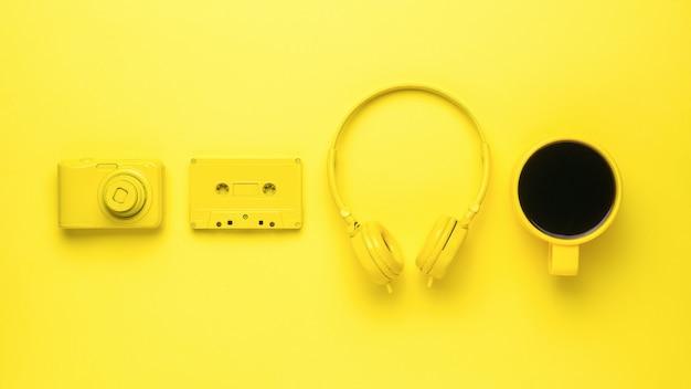黄色のカメラ、ヘッドフォン、カセットテープ、黄色の背景にコーヒー1杯。カラートレンド。