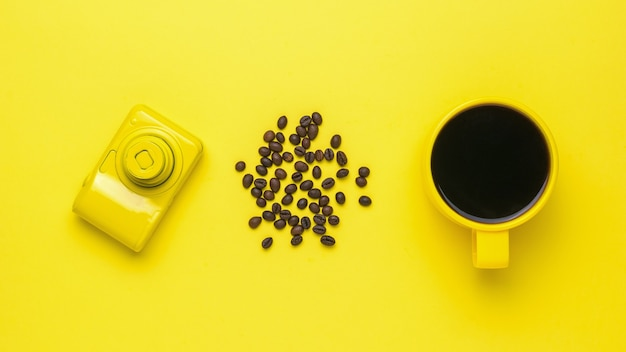 A yellow camera, a yellow cup of coffee and coffee beans on a yellow background. a popular hot drink and equipment for creativity. flat lay.