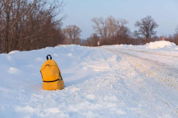 A yellow camping backpack filled with things is standing on the snow on the side of the road. hitchhiking concept in winter