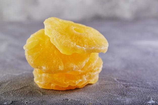 灰色のコンクリート表面に黄色の砂糖漬けのパイナップルリング