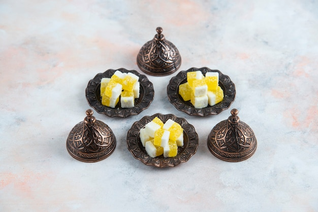 Yellow candies on crockery over white surface