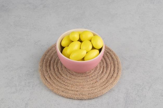 大理石の表面のトリベットのカップに黄色いキャンディー