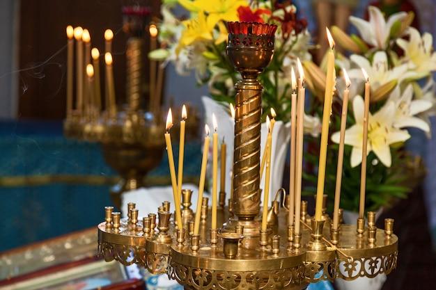 Желтая свеча зажгла огонь для поклонения. горящие восковые свечи в церкви