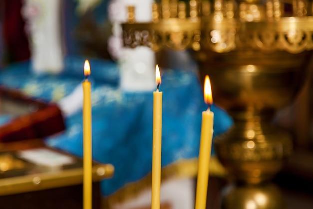 노란색 촛불은 예배를 위해 불을 붙였습니다. 교회에서 왁스 초를 태우고 있습니다.