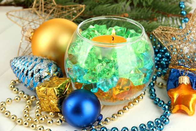 Yellow candle with christmas decoration on light background
