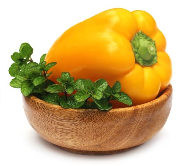 Желтый перец с листьями мяты на миске