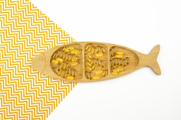 Желтые капсулы омега-3 лежат на деревянной тарелке в виде рыбы.