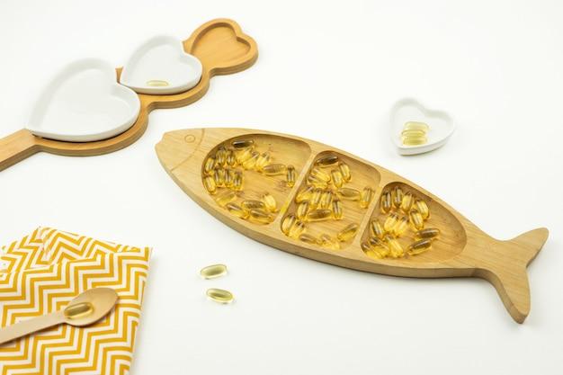 Желтые капсулы омега-3 лежат на деревянной тарелке в виде рыбки.