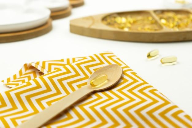 Желтые капсулы омега-3 лежат на деревянной ложке