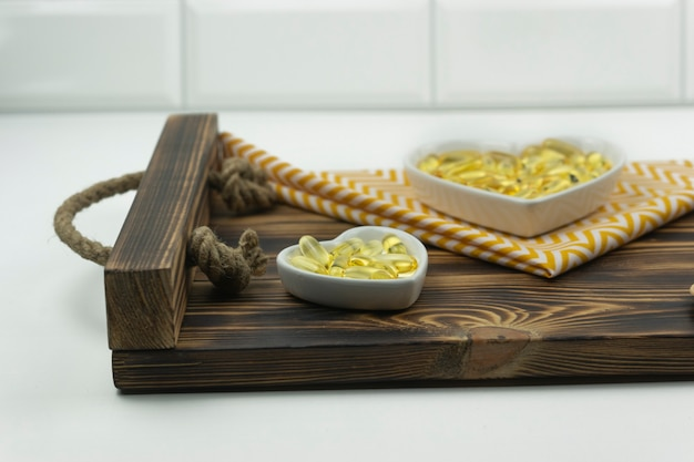 Желтые капсулы омега 3 лежат на белых керамических тарелках в виде сердечек на деревянном подносе.