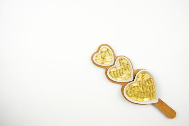 Желтые капсулы омега-3 лежат на белых керамических тарелках в форме сердечек.