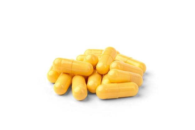 Желтые капсулы или таблетки, изолированные на белом фоне.