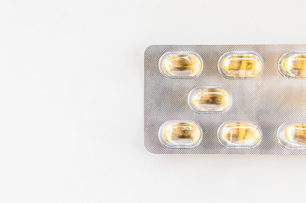 Yellow capsules packed in a blister pack isolated