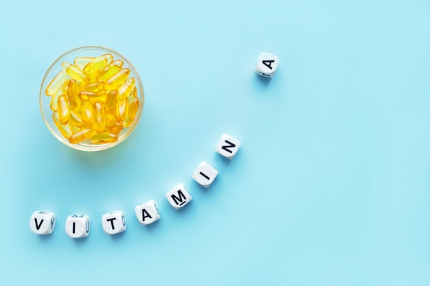 Yellow capsules in the round glass bowl and the word vitamin a