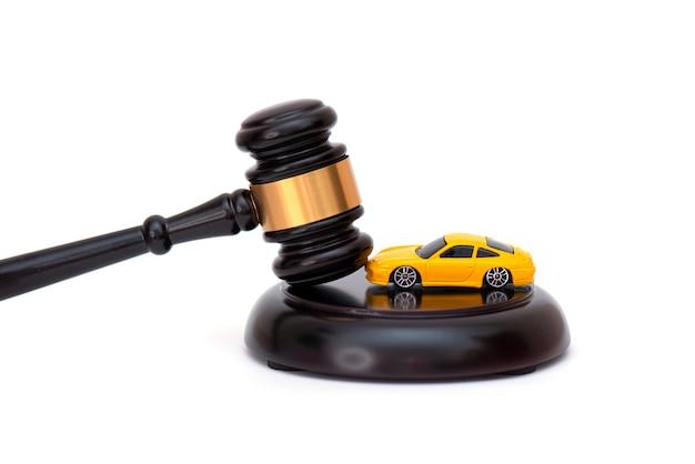白で隔離される木製の裁判官の小槌の黄色い車、車の信用債務または離婚についての概念図。