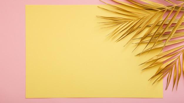 황금 야자수 잎으로 만든 프레임의 텍스트를 위한 노란색 카드 복사 공간. 열 대 야자수는 분홍색 배경에 둡니다. 여름 꽃 배경에 금색을 칠했습니다. 복사 공간이 있는 긴 웹 배너입니다.