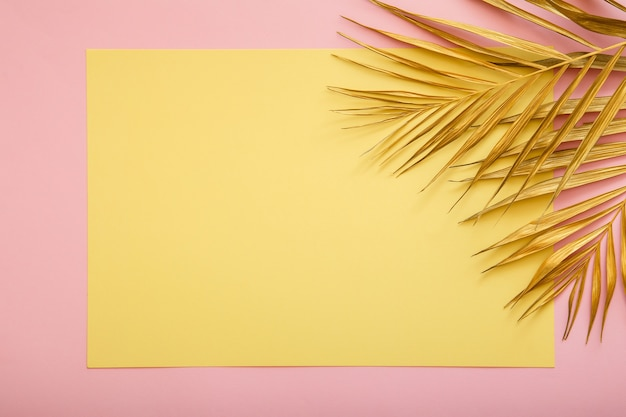 Yellow card copy space for text in frame golden palm leaf. tropical palm leave summer background