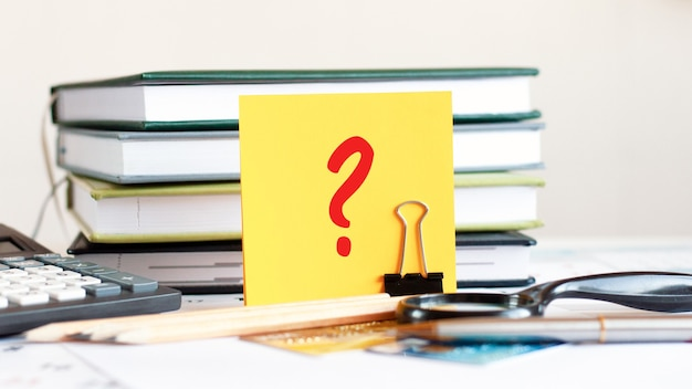 A yellow card with the question mark stands on a clip for papers on the desk against the background of books, selective focus