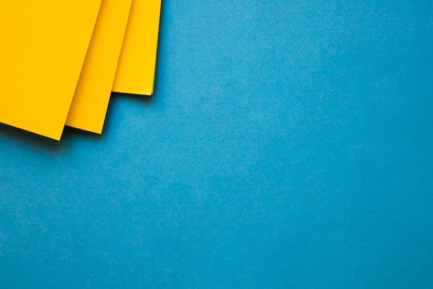 Carte di cartone giallo all'angolo del contesto blu