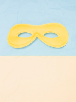 Yellow carnival mask above dual backdrop