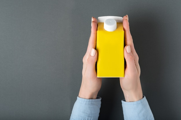 Yellow carton box or packaging of tetra pack with a cap in a female hands.