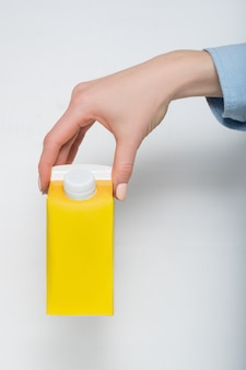 Yellow carton box with a cap in a female hand.