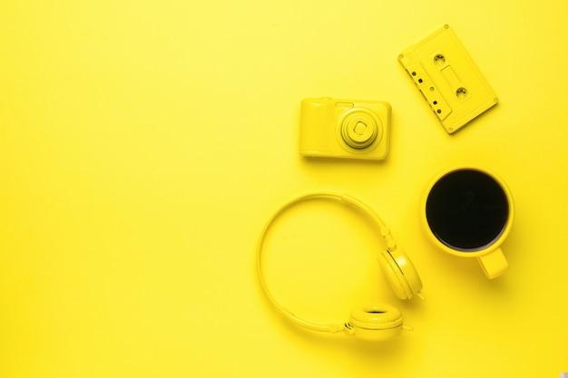 노란색 배경에 노란색 카세트, 헤드폰, 카메라, 커피 머그. 컬러 트렌드. 세련된 액세서리. 텍스트에 대 한 장소입니다.