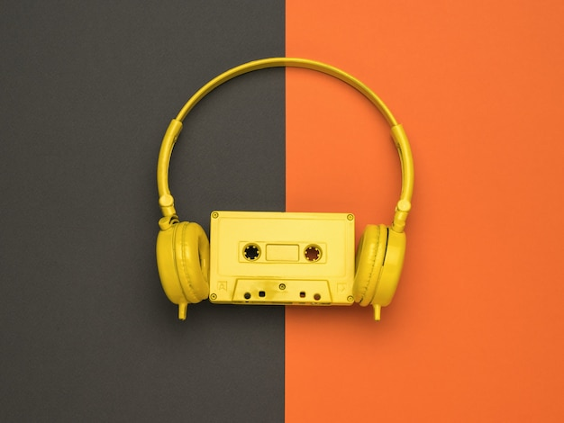 A yellow cassette with a magnetic tape and yellow headphones on an orange and black background. color trend. flat lay.