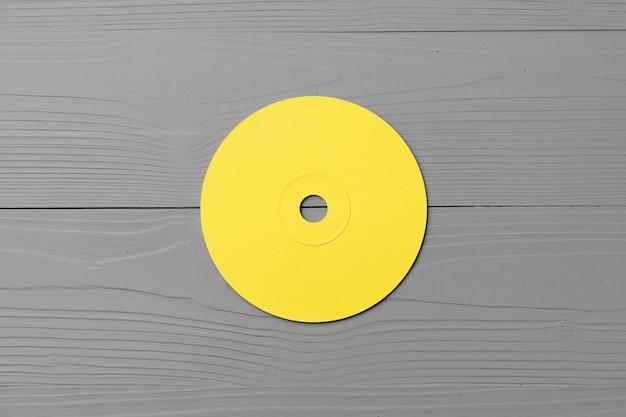 Желтый cd-диск на сером деревянном