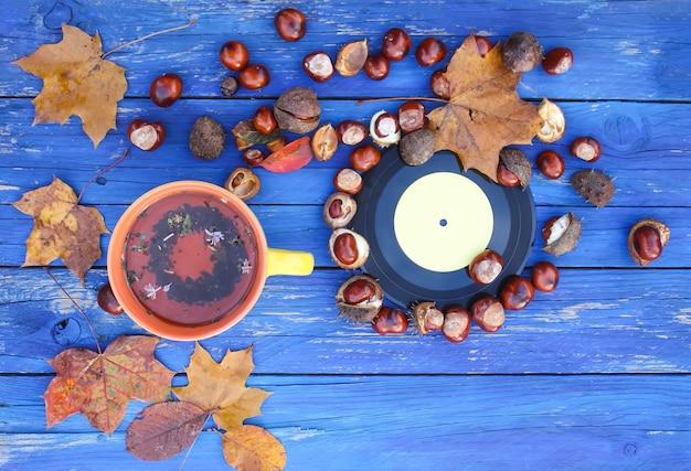 秋の紅葉と栗の古い木製の背景にハーブティーとヴィンテージビニールレコードの黄色いセラミックカップ。