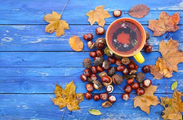 秋の紅葉と栗と熟成した木製の背景にハーブティーの黄色いセラミックカップ。