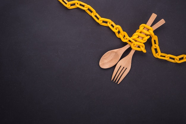 Yellow chain locked around the wooden spoon and fork