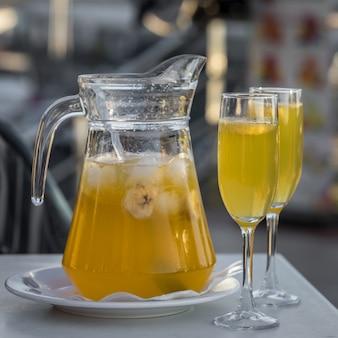 Сангрия желтого шампанского подается в кружке с двумя стаканами