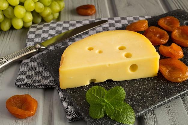 黄色のチーズと木製の灰色のドライアプリコット