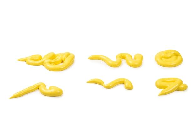 Брызги соуса желтого сыра, изолированные на белом фоне.