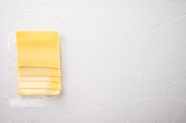 흰 돌에 플라스틱 팩에 체다 세트의 노란색 치즈 조각