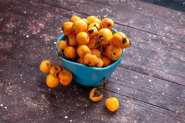 Желтая вишня спелая, свежая и спелая в синей миске на коричневом