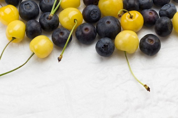 Yellow cherry and blueberry on white background. flat lay  copy space.