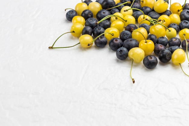 Yellow cherry and blueberry on white background.