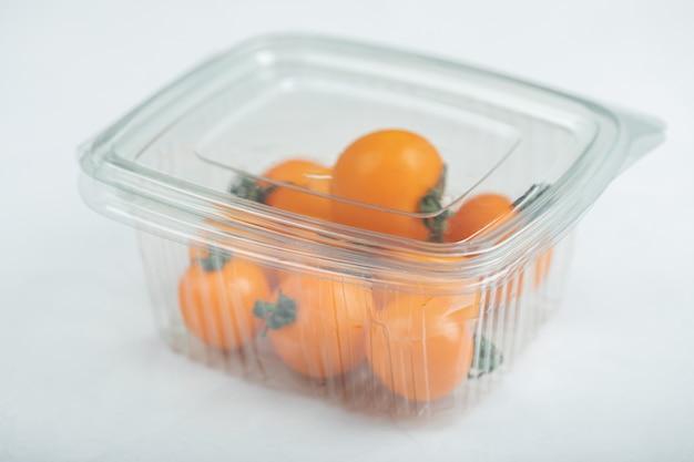 플라스틱 용기에 노란색 체리 토마토. 고품질 사진