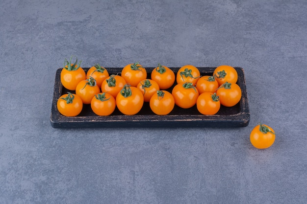 Yellow cherry tomatoes isolated on blue surface