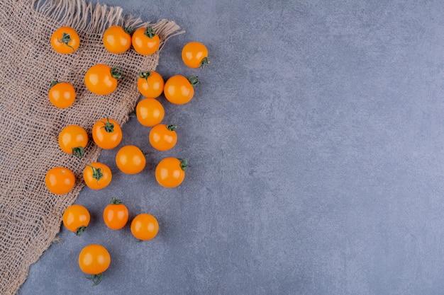 Pomodorini gialli isolati su superficie blu
