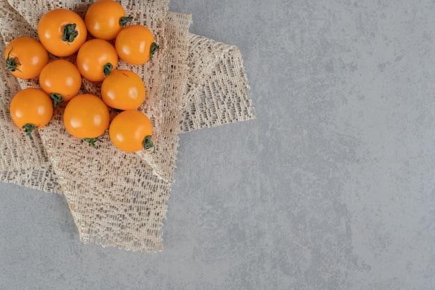 Pomodorini gialli isolati su superficie di cemento