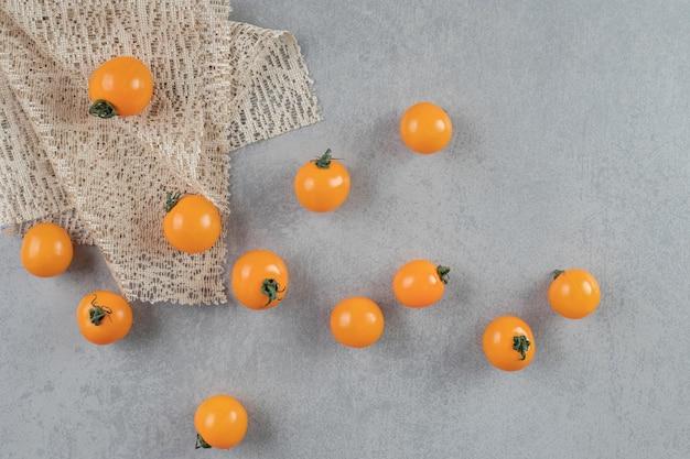 Желтые помидоры черри, изолированные на бетонном столе.